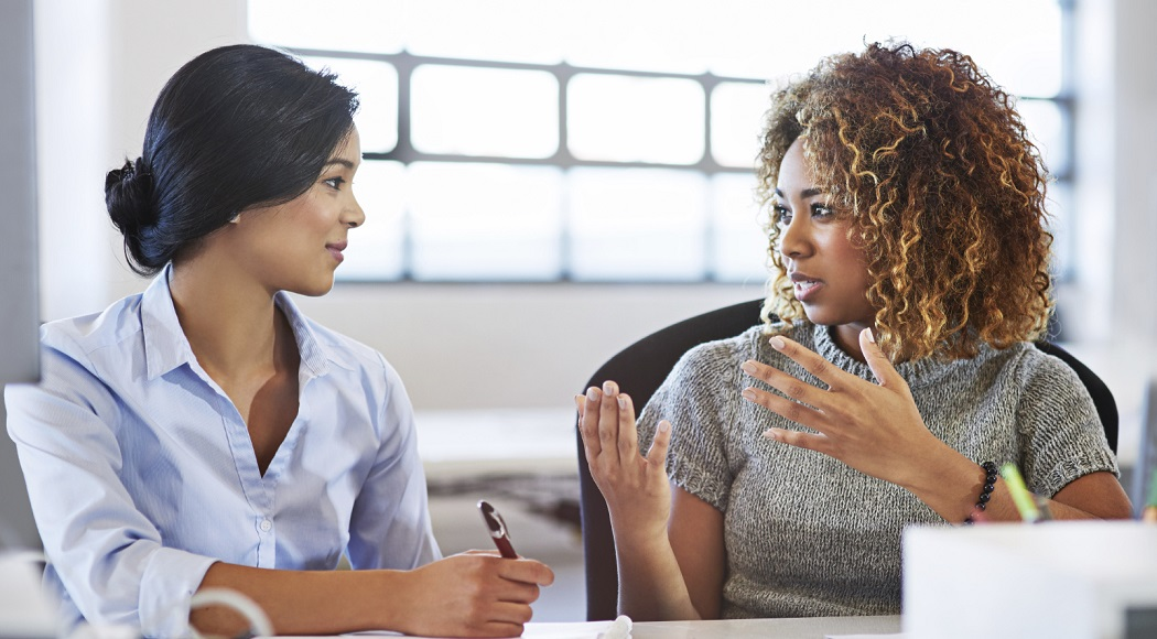 Two businesswomen discuss matters one-on-one, up close